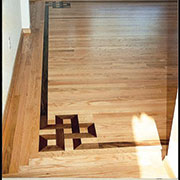 Knot accent with log cabin border, flush floor vent in private residence. Mountain Lake, SC