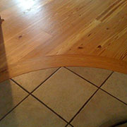 All Wood Floorcraft shop made BENT heart pine header to tile, private 		residence, Hickory, NC